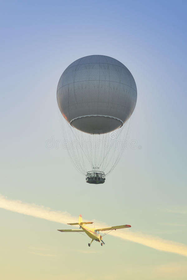 Gas Balloon and Yellow Aircraft against the Sky stock photos