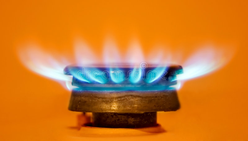 Gas burner. Metal gas burner with a blue flame on an orange background stock photo