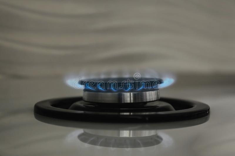 Gas burner with blue flame on modern stove, closeup royalty free stock photography