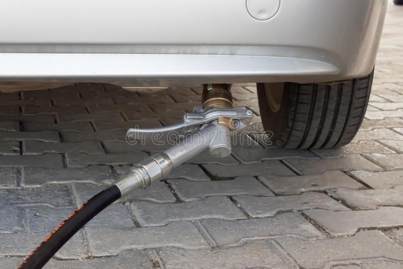 Gas filling from vehicle bumper and gas pump. At fuel station royalty free stock photos