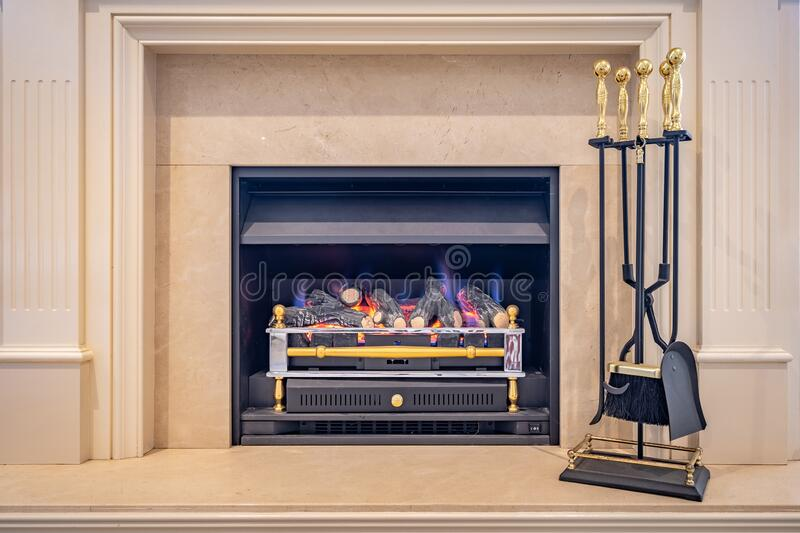 Gas fired classic looking fireplace with tools on the side. Gas fired classic looking indoor fireplace with tools on the side royalty free stock photos
