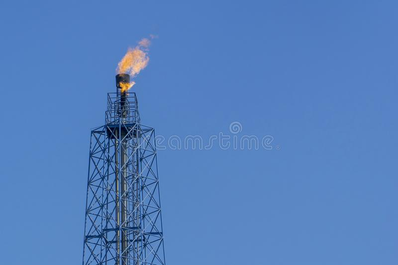 Gas flares in petroleum refinery with blue sky background royalty free stock photo