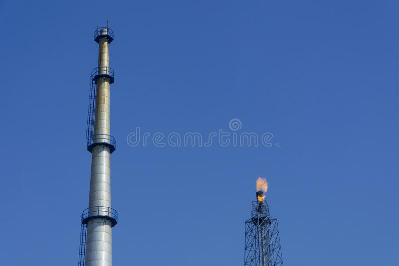 Gas flares in petroleum refinery with blue sky background.  stock photos