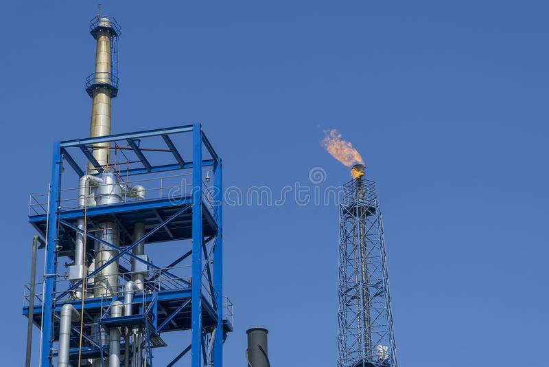 Gas flares in petroleum refinery with blue sky background.  stock images