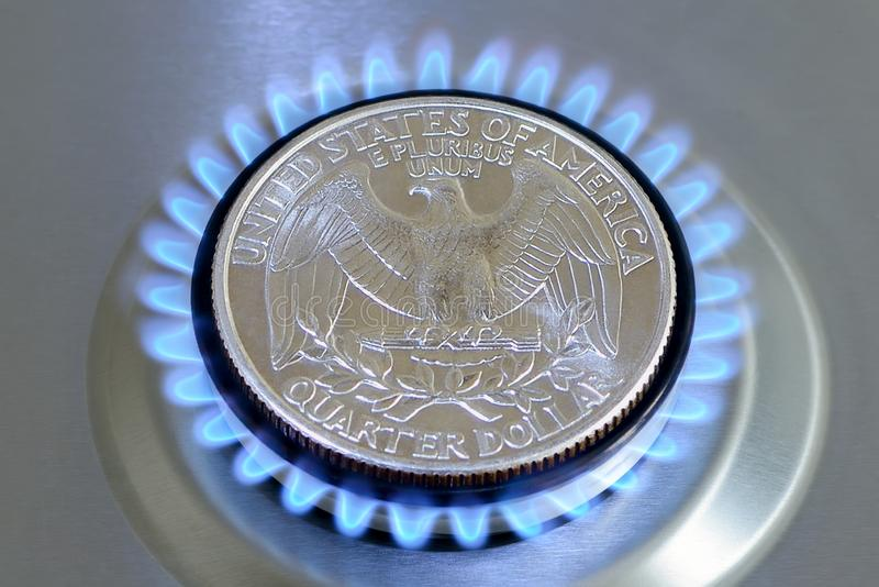 Gas hob with burning natural gas and quarter dollar coin. Gas hob with burning natural gas and quarter US dollar coin. The concept of the struggle for global gas royalty free stock images