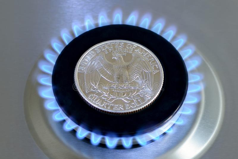 Gas hob with burning natural gas and quarter dollar coin. Gas hob with burning natural gas and quarter US dollar coin. The concept of the struggle for global gas royalty free stock photography
