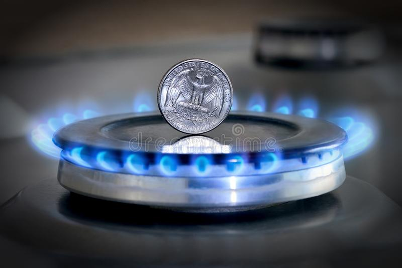 Gas hob with burning natural gas, quarter US dollar coin. Gas hob with burning natural gas and quarter US dollar coin. The concept of the struggle for global gas royalty free stock photography