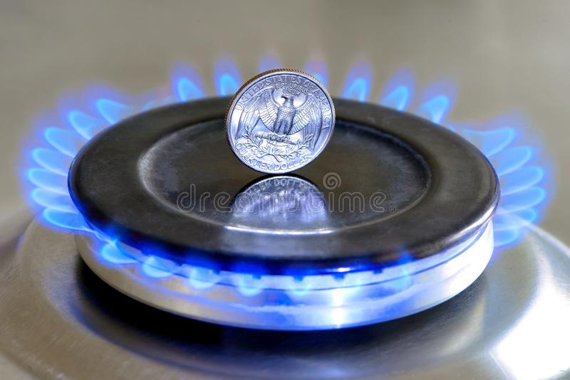 Gas hob with burning natural gas, quarter US dollar coin. Gas hob with burning natural gas and quarter US dollar coin. The concept of the struggle for global gas stock photography
