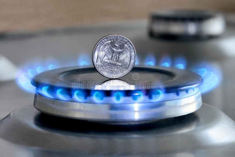 Gas hob with burning natural gas, quarter US dollar coin. Gas hob with burning natural gas and quarter US dollar coin. The concept of the struggle for global gas stock image