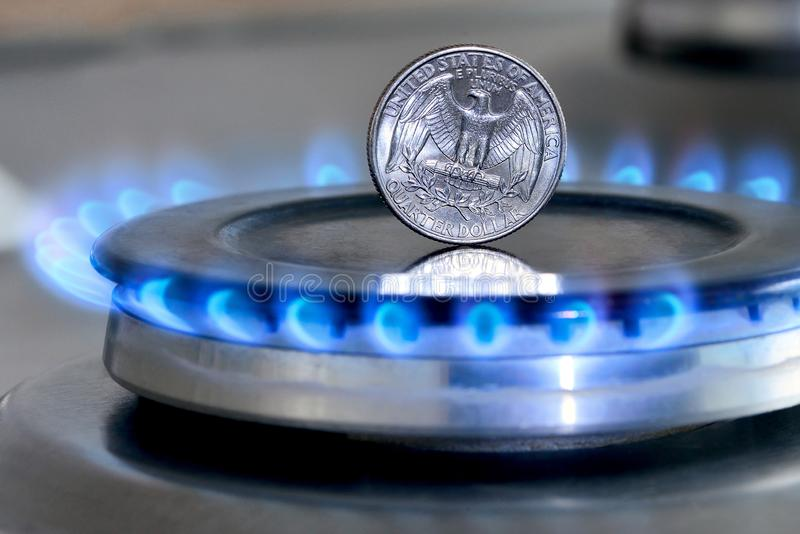 Gas hob with burning natural gas, quarter US dollar coin. Gas hob with burning natural gas and quarter US dollar coin. The concept of the struggle for global gas royalty free stock photo