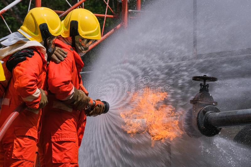 Gas leak from pipe and valv.flame from gas leak fire fighting with extingguishers and fire hose.fighters in action at gas Fire. Gas leak from pipe and valv.flame stock photography