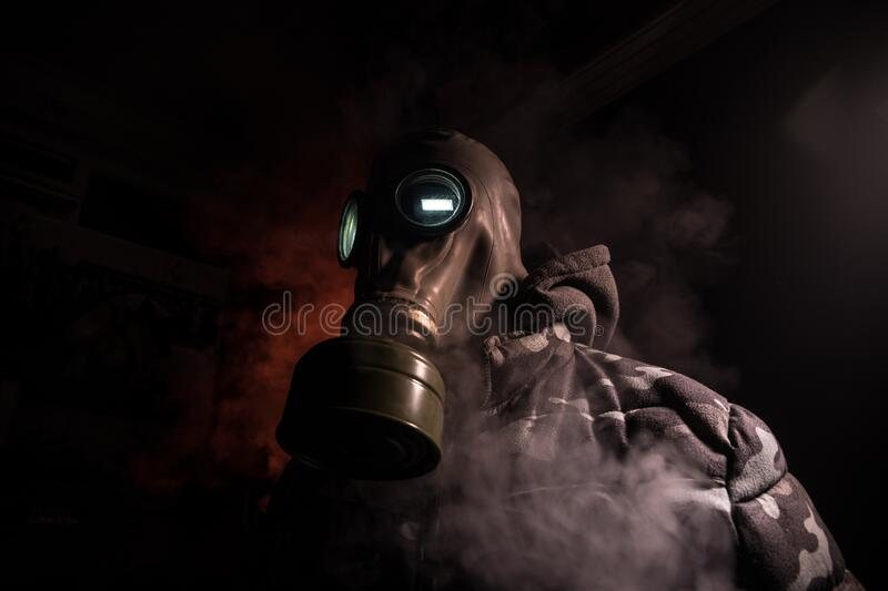 Gas mask with clouds of smoke on a dark background. Sign of radioactive contamination. Means for radiation protection. Danger of. Environmental disaster. Post stock photos