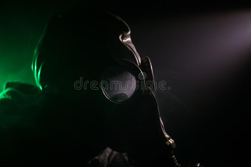 Gas mask with clouds of smoke on a dark background. Sign of radioactive contamination. Means for radiation protection. Danger of. Environmental disaster. Post royalty free stock photos