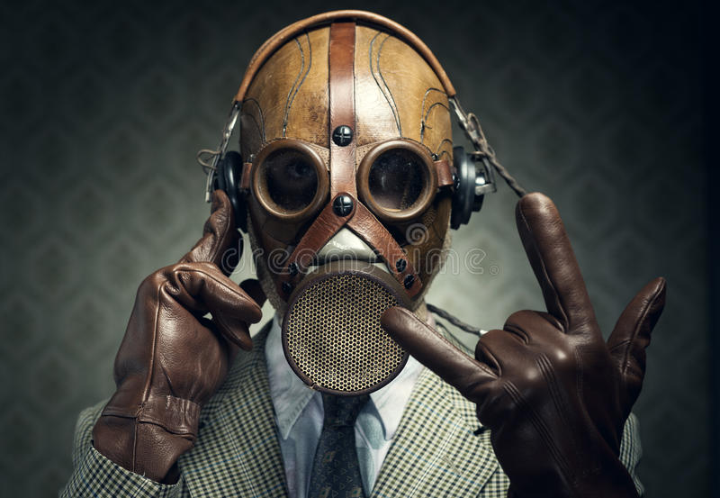 Gas mask rock. Man wearing gas mask and headphones making rock sign royalty free stock photo