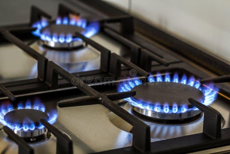 A gas naturale sulla stufa di gas della cucina nello scuro Il pannello dall'acciaio con un bruciatore di anello del gas su un fon immagine stock libera da diritti