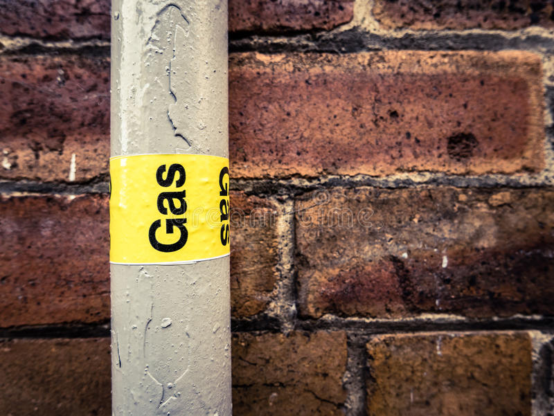 Gas Pipe. Detail Of A Residential Gas Pipe Against A Red Brick Wall stock photos