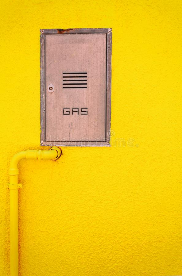 Gas pipe and a manhole in a bright yellow wall, vertical compositon royalty free stock images