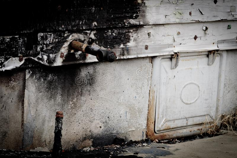 Gas pipe on side of burned house royalty free stock images