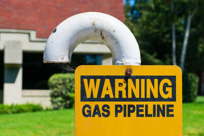 Gas pipeline warning sign on white bended pipe with blurred background of green landscape and commercial office building.  stock image
