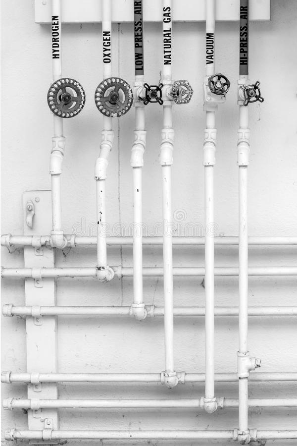 Gas Pipes & Antique Valves Pattern on laboratory wall. Vintage gas pipes and antique valves in science lab - hydrogen, oxygen, natural gas, vacuum, air. Black royalty free stock images