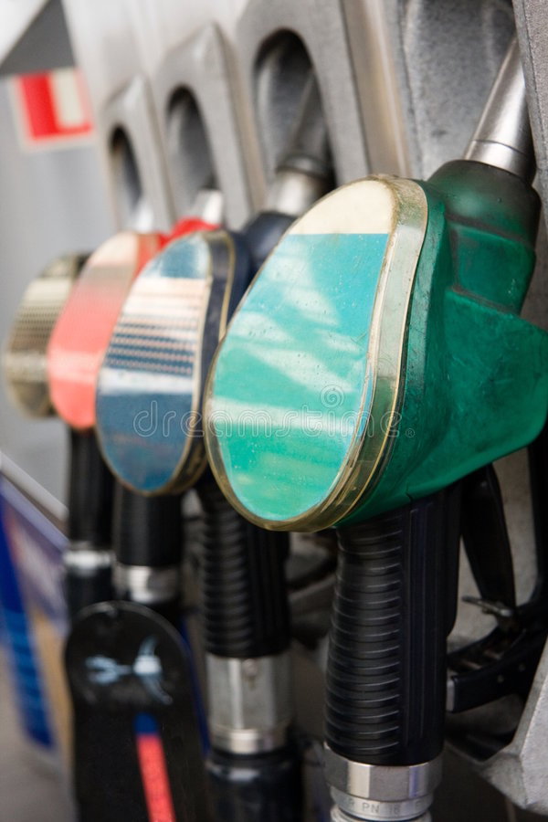 Gas pump nozzles. Colorful gas pump nozzles on gas-station stock photography