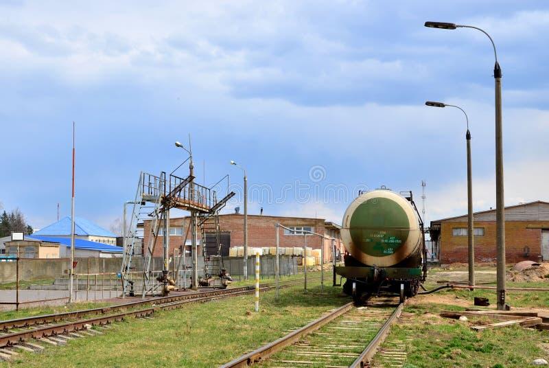 GASERO del coche del tanque por el carril en los tanques de almacenamiento de aceite en terminal del combustible Descarga del gas foto de archivo libre de regalías