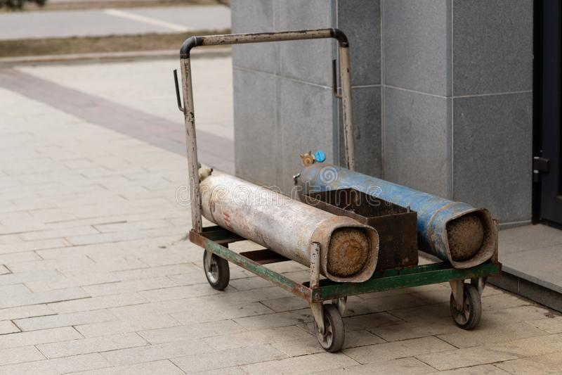 Gasflessen voor lassen op een karretje dichtbij het gebouw stock foto's