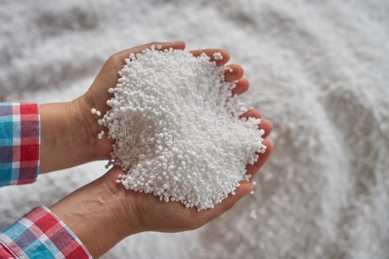 Gasformigt grundämnegödningsmedel eller ureagödningsmedel i bondehand vit gödningsmedelbakgrund för suddighet royaltyfri fotografi