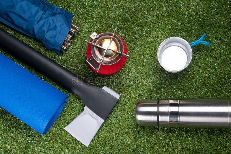 Gasfornuis, bijl, yogamat, thermosflessen, op grasachtergrond royalty-vrije stock afbeelding