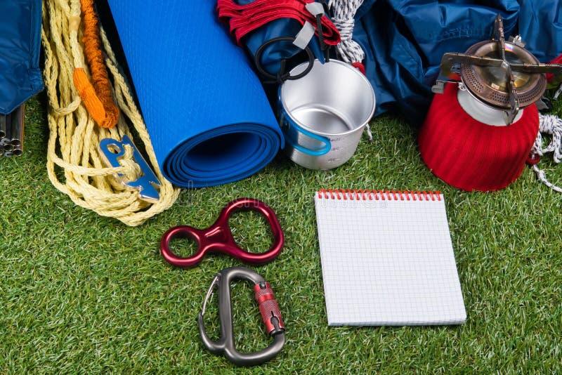 Gasgasbrännaren, handyxafilten för yoga, rånar, tältet, carabiner för försäkring, repet och notepaden för att anteckna arkivbilder