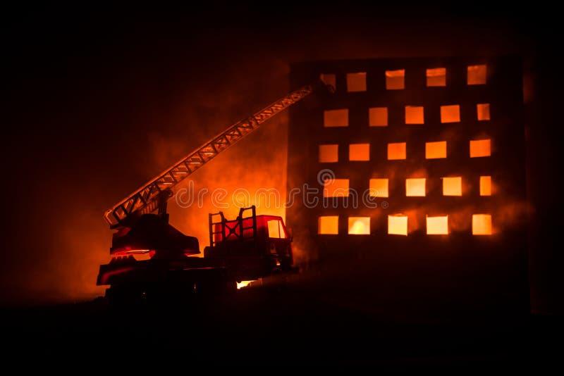 Gasi ogienia intymny dom przy nocą Zabawkarski samochód strażacki z długą drabiną i płonący budynek przy nocą Pożarniczego alarma zdjęcie royalty free