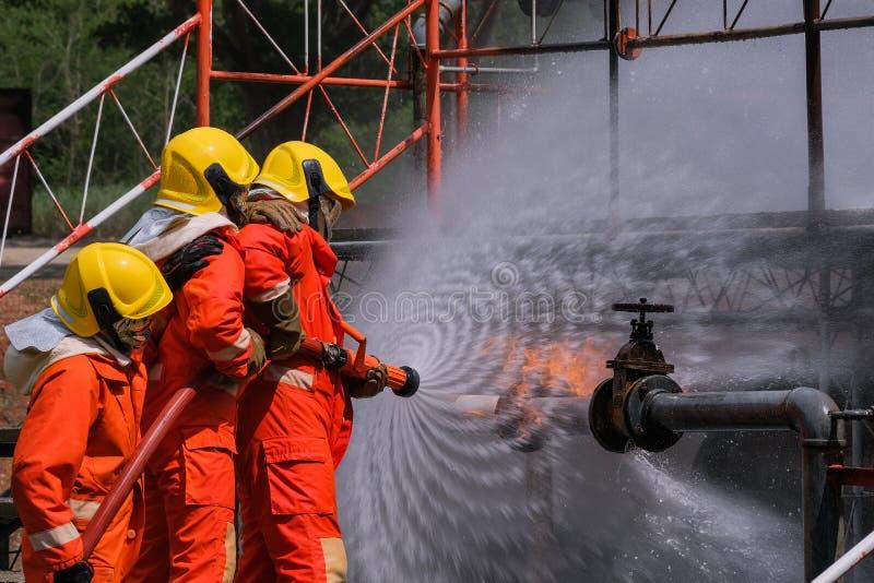 Gasleck vom Rohr und von valv Flamme vom Gasleck Feuerbekämpfung mit extingguishers und Feuerlöschschlauch Kämpfer in der Aktion  lizenzfreies stockbild