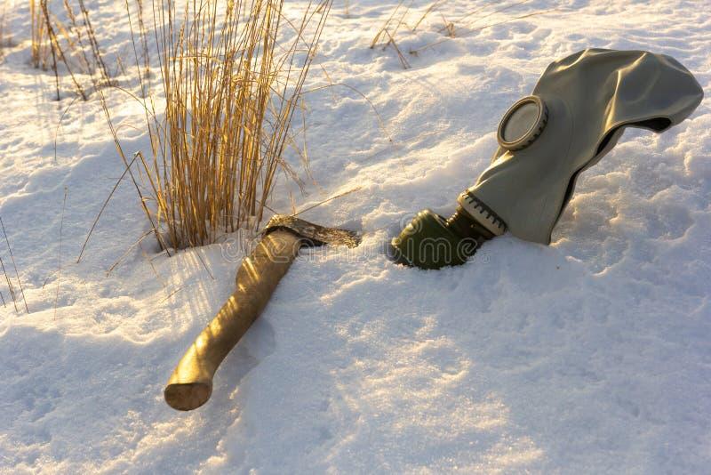 Gasmaske und Axt im Schnee auf dem Feld mit trockenem Gras, der Krieg im Winter stockfoto