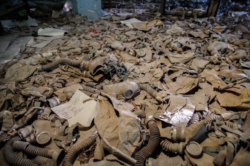 Gasmasks som lägger på golvet i skolan av Pripyat, Tjernobyl zon arkivbilder