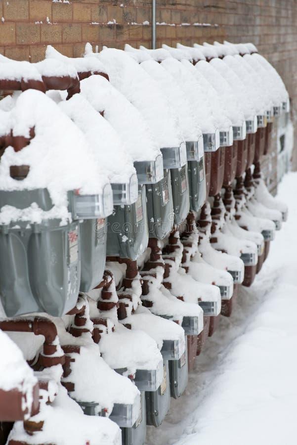 Gasmeters met sneeuw op de muur worden behandeld die royalty-vrije stock afbeeldingen