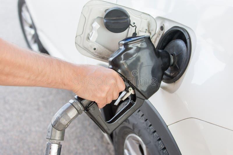 Gasolina de derramamento no tanque do carro fotografia de stock