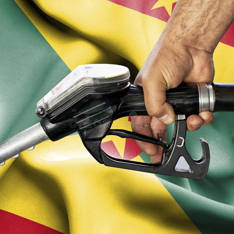 Gasoline consumption concept - Hand holding hose against flag of Guernsey stock image
