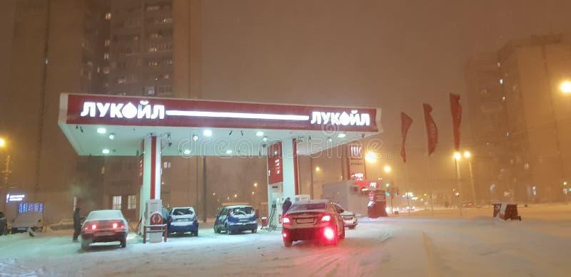 Gasolinera de Lukoil por la tarde del invierno en nevadas imagen de archivo