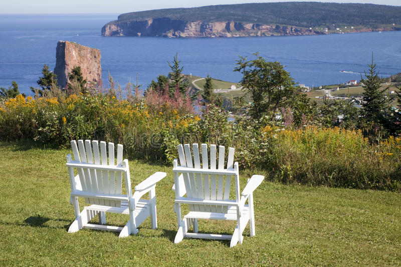 Gaspe. A high overlook with too Adirondack chairs considering a view of Perce Rock, the Gulf of St. Lawrence and the Gaspe royalty free stock photo