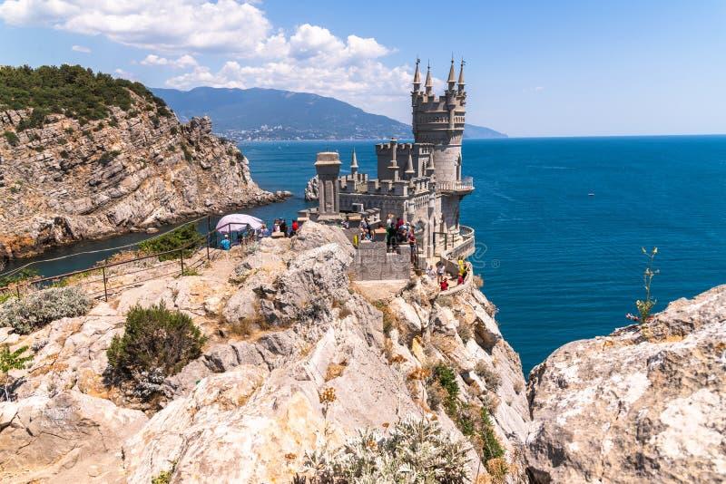 Gaspra Krim - Juli 7 2019 Slotten av svalor bygga bo på udden Ai-Todor av den Black Sea kusten arkivbild