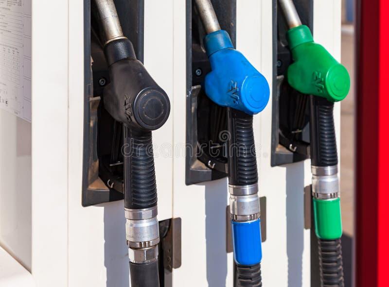 Gaspumpendüsen mit verschiedenen Brennstoffen an der Tankstelle lizenzfreies stockbild