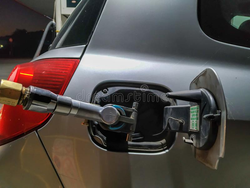 Gasschlauch pumpen Gas in Grauwagen während der Nachtfahrt Nachfüllen von Gas für zusätzliche Energie und Energie stockbilder