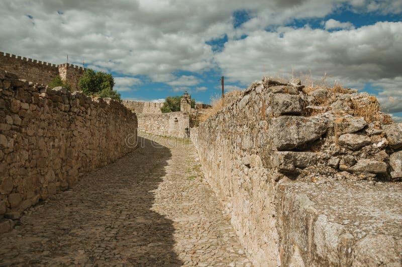 Gasse mit Steinwänden in Richtung zum Schloss von Trujillo stockfotos