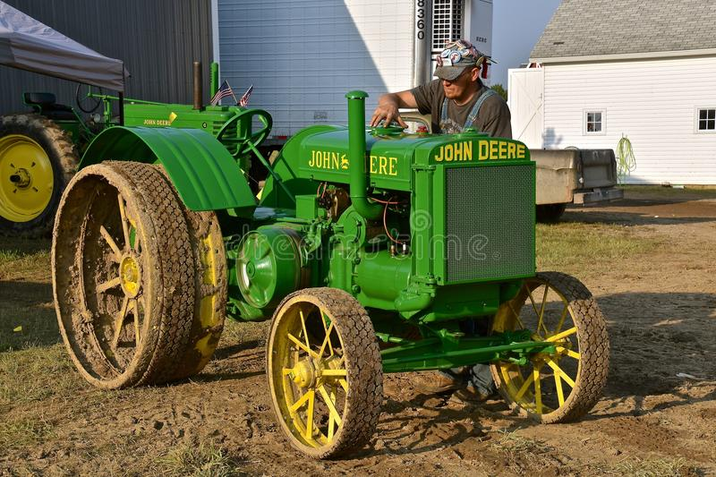 Gassing up an old restored John Deere D tractor. ROLLAG, MINNESOTA, Sept 1, 2017: A restored John Deere D tractor is being filled with gasoline by the royalty free stock images