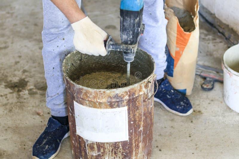 gastarbeider de meester kneedt de oplossing voor het pleisteren Metaalemmer Natuurlijk proces royalty-vrije stock foto