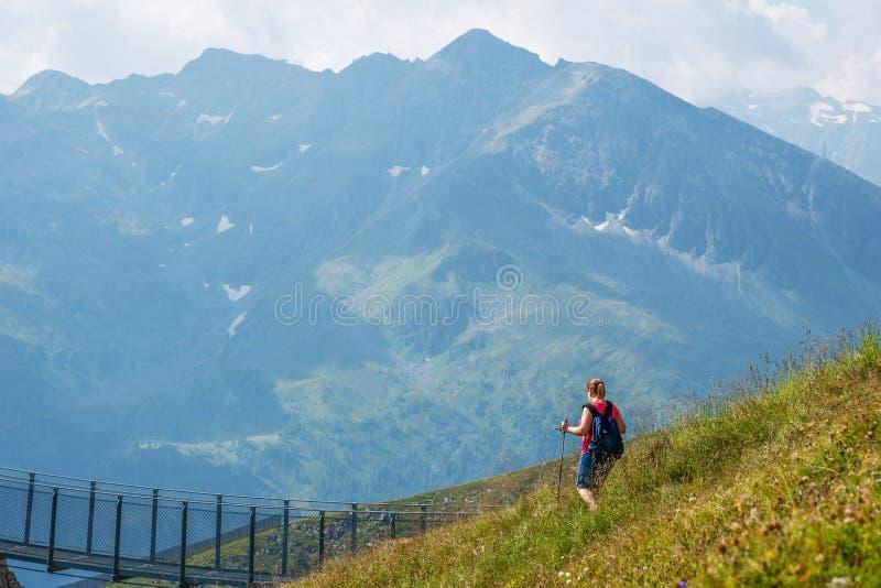 GASTEIN MAU, ÁUSTRIA - 6 DE AGOSTO DE 2018: Caminhante fêmea que caminha abaixo dos montes alpinos com pregos foto de stock