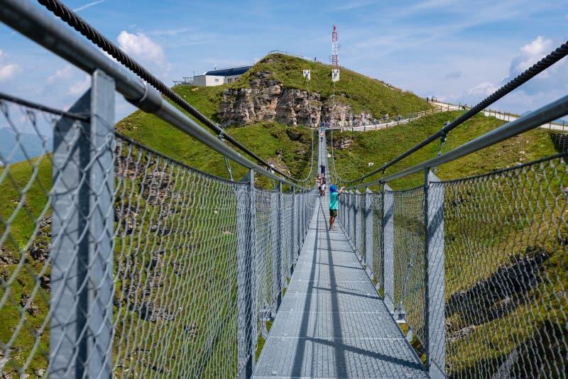 GASTEIN MAU, ÁUSTRIA - 6 DE AGOSTO DE 2018: Os povos cruzam uma ponte de suspensão no Stubnerkogel, montanhas de Gastein, Áustria fotos de stock royalty free