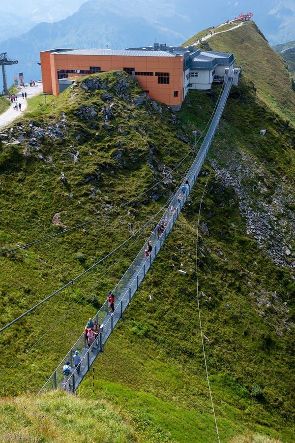GASTEIN MAU, ÁUSTRIA - 6 DE AGOSTO DE 2018: Os povos cruzam uma ponte de suspensão no Stubnerkogel, montanhas de Gastein, Áustria fotografia de stock