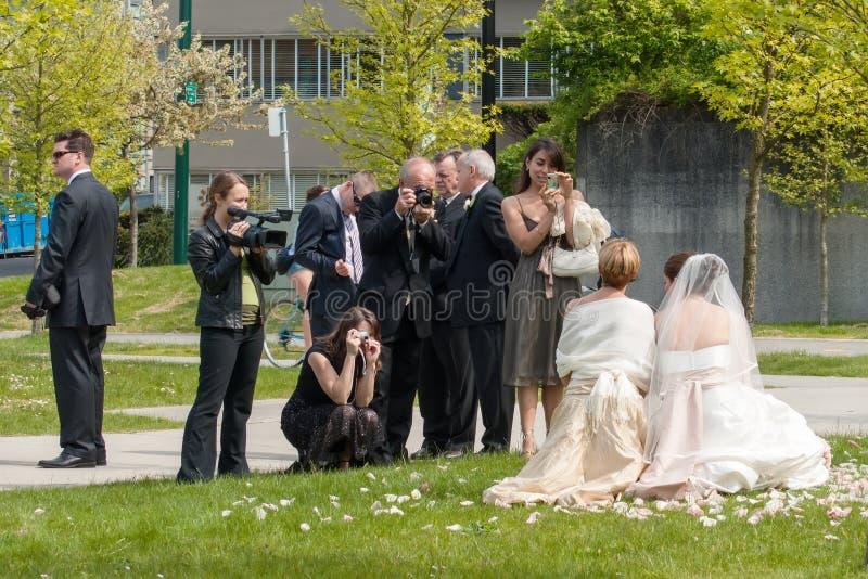 Gasten en familie die foto's van bruid nemen stock foto's