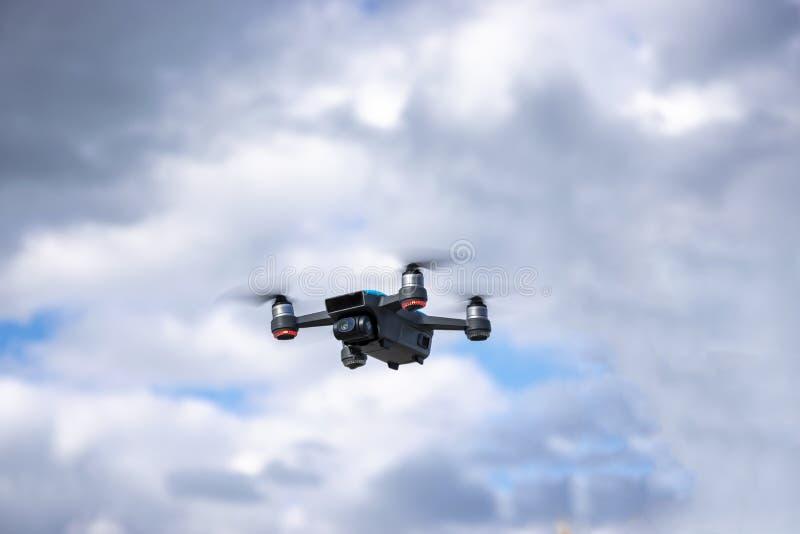 Gastos indirectos que vuelan del abej?n en cielo azul nublado foto de archivo